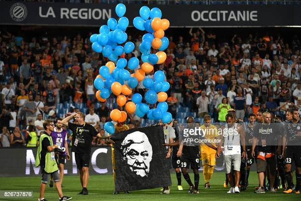 Montpellier's players hold a portrait of Montpellier's late president Louis Nicollin after the French L1 football match between MHSC Montpellier and...