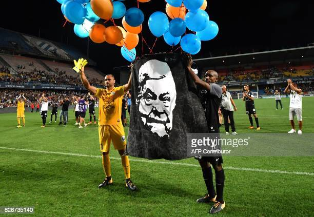 Montpellier's Senegalese forward Souleymane Camara and Montpellier's French goalkeeper Laurent Pionnier hold a portrait of Montpellier's late...