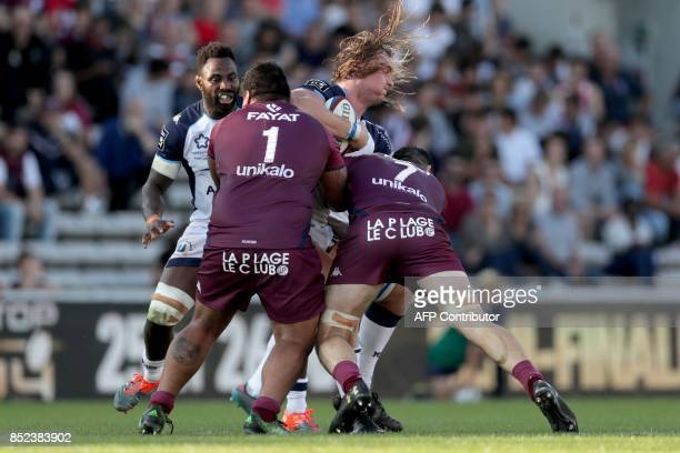 Montpellier's South African lock Jacques Du Plessis is tackled by Bordeaux's French prop Sebastien Taofifenua and French number 8 Loann Goujon during...