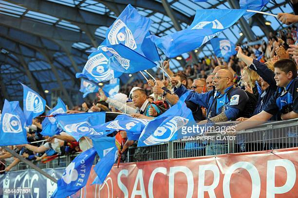 Montpellier's supporters wave flags after after the French Top 14 rugby union match between Grenoble and Montpellier on April 12 2014 at the Stade...