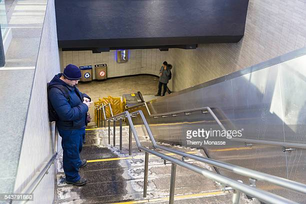Montréal Québec Canada January 5 2016 A man is looking at his smartphoneat the entrance of the JeanTalon metro station in the Montreal Metro The...
