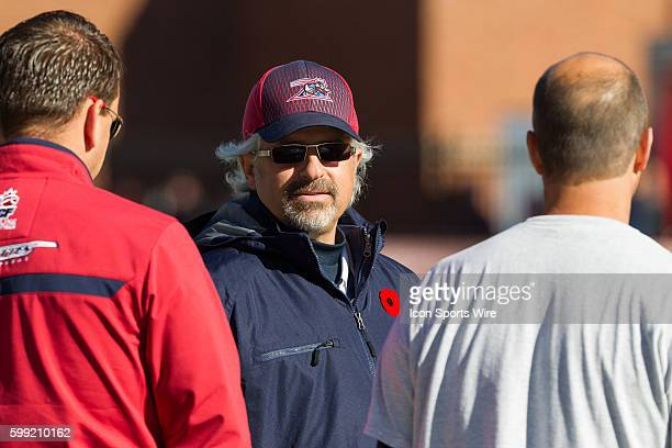 Montreal Alouettes general manager Jim Popp talks with staff members prior to the game between the Toronto Argonauts and the Montreal Alouettes at...