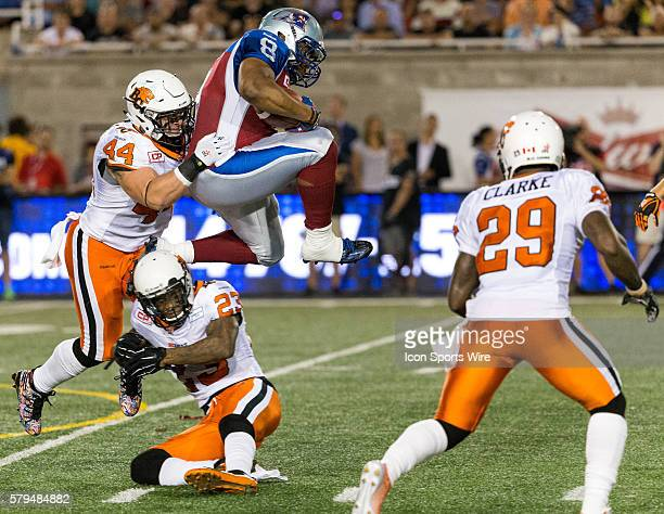 Montreal Alouettes slotback Nik Lewis jumps over BC Lions defensive back Josh Johnson during a CFL game between the BC Lions and the Montreal...