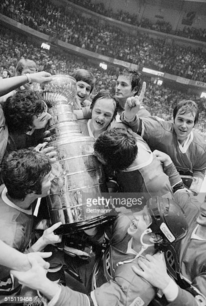Montreal Canadien goalkeeper Ken Dryden gives the 'number one' gesture while his teammates hug and kiss the Stanley Cup following their fourgame...