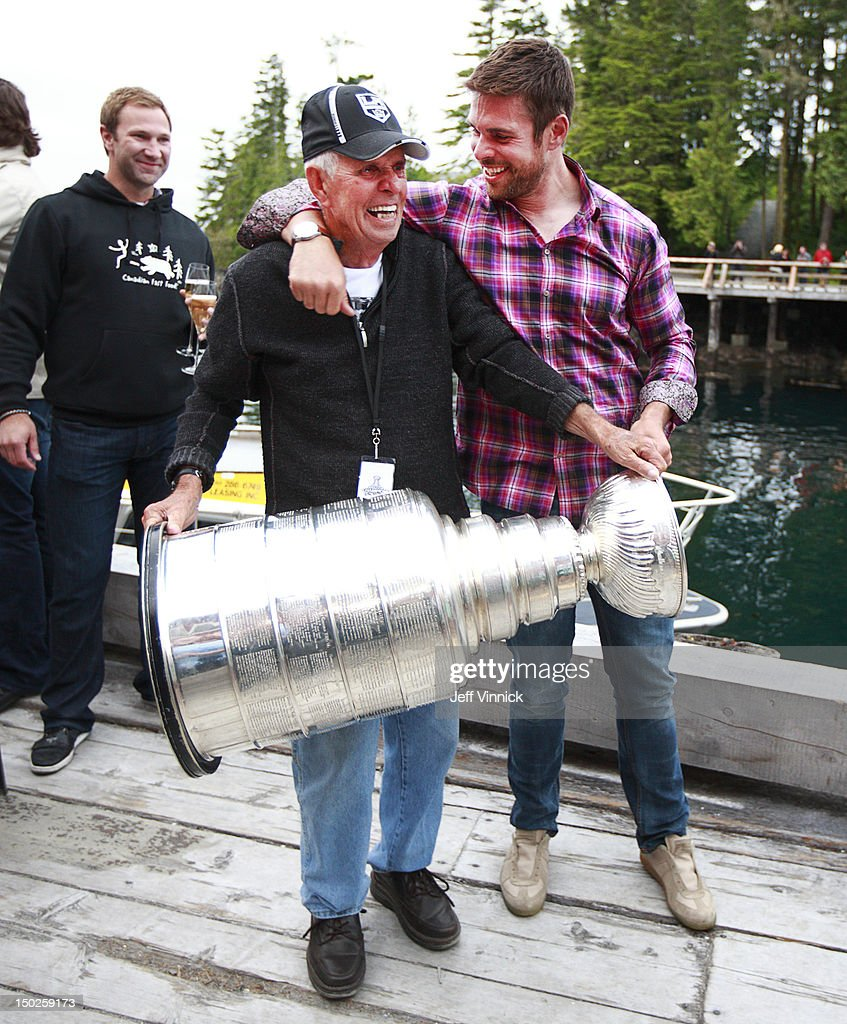 Montreal Canadiens Eric Cole looks on as Willie Mitchell #33 of the Los Angeles Kings and his grandfather Lester Mitchell hold the Stanley Cup during a family party August 12, 2012 in Telegraph Cove, British Columbia, Canada. Mitchell took the Stanley Cup to his hometown of Port McNeill, B.C. for his one-day celebration with the prized trophy.