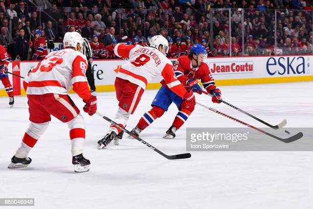 Montreal Canadiens Left Wing Charles Hudon tries to gain control of the puck and get away from Detroit Red Wings Right Wing Justin Abdelkader during...