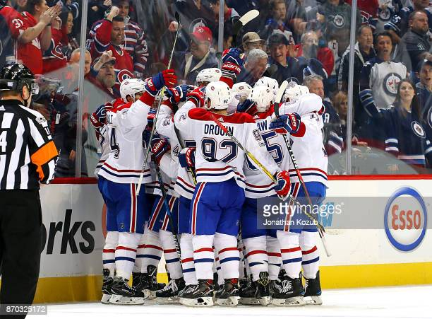 Montreal Canadiens players mob teammate Max Pacioretty following an overtime goal against the Winnipeg Jets at the Bell MTS Place on November 4 2017...