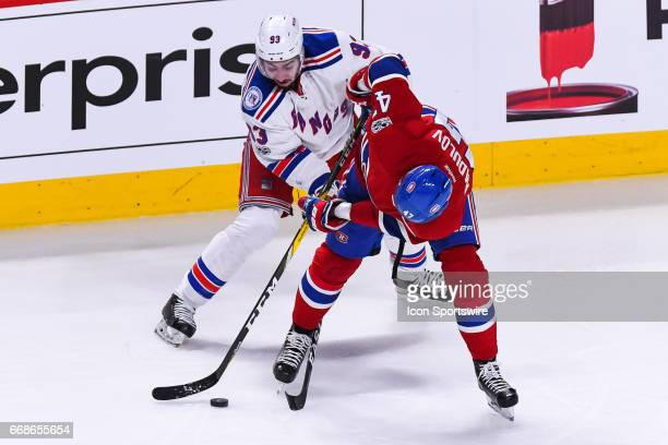 Montreal Canadiens right wing Alexander Radulov and New York Rangers center Mika Zibanejad ref52 battling to control the puck during game 2 of the...