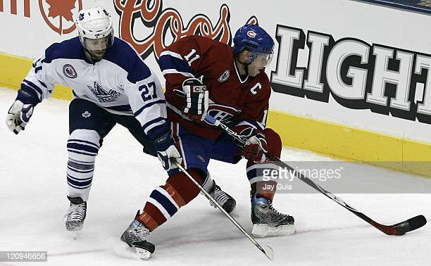 Montreal Canadiens Saku Koivu turns to avoid the close checking of Toronto Maple Leafs Michael Peca in action at the Air Canada Centre in Toronto...