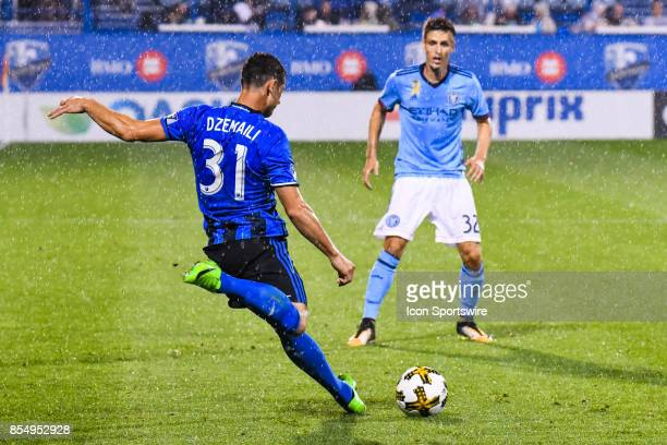 Montreal Impact midfielder Blerim Dzemaili passes the ball under the rain in front of New York City FC defender Andraz Struna during the New York...