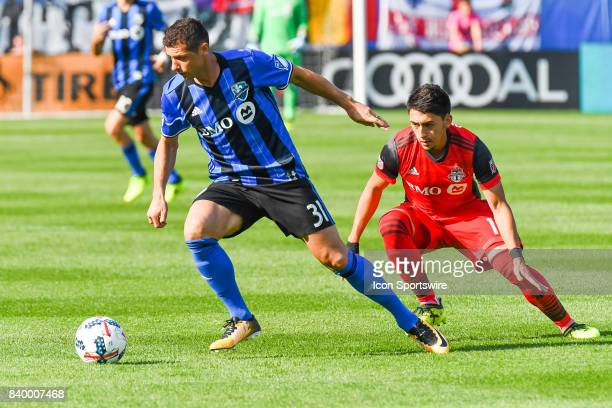 Montreal Impact midfielder Blerim Dzemaili tries to get away from Toronto FC defender Jason Hernandez during the Toronto FC versus the Montreal...