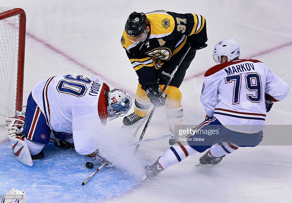 Montreal's Andrei Markov (#79), right, sprays his goalie, Peter Budaj, as he stops in front of the net, which didn't help the net minder keep an eye on the puck, and the Bruins' Patrice Bergeron (#37), center, pushed it past him for a second period Boston goal. The Boston Bruins hosted the Montreal Canadiens in a regular season NHL hockey game at the TD Garden.