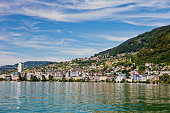 A view of the city of Montreux on the shores of Lake Geneva from a ship on the water on a lazy summer afternoon.