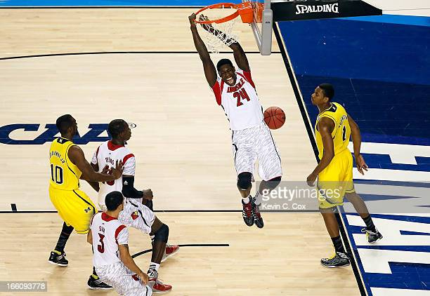 Montrezl Harrell of the Louisville Cardinals dunks an alleyop pass in the first half against Glenn Robinson III of the Michigan Wolverines vduring...