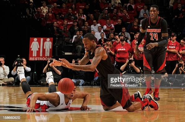 Montrezl Harrell of the Louisville Cardinals watches teammate Kevin Ware fight for a loose ball against Percy Blade of the Western Kentucky...