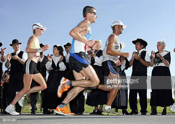 French Corinne Raux and other marathon competitors run in front of traditional Breton dancers during the eight edition of the MontSaintMichel...