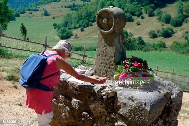 woman meditating before the stele 'Camp dels Cremats'