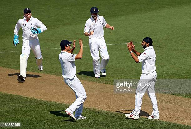Monty Panesar of England celebrates his wicket of Ross Taylor of New Zealand with Alastair Cook during day two of the Third Test match between New...