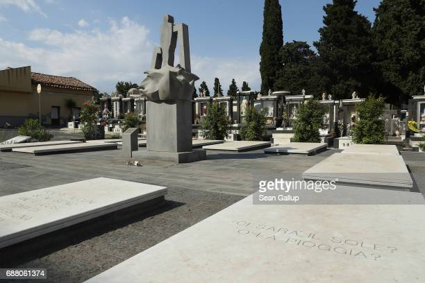 A monument stands among tombs that contain the bodies of migrants who died while trying to reach Italy in the municipal cemetery on the island of...