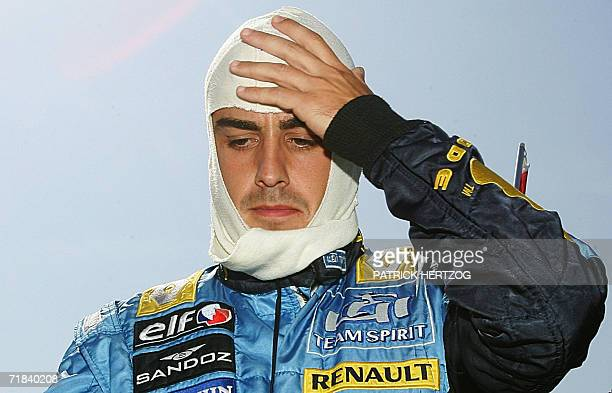 Spanish Renault driver Fernando Alonso puts his balaclava on in the grid of the Monza racetrack before the Italian Formula One Grand prix 10...