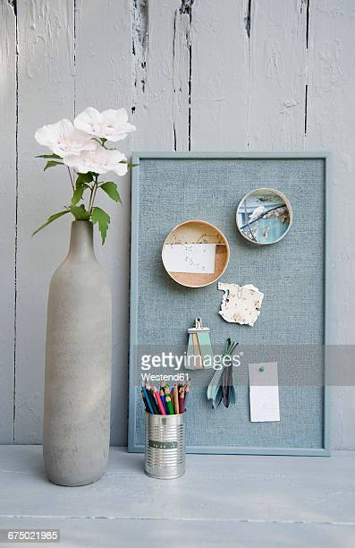 Mood board with photos,coloured pencils, hibiscus blossoms, vase