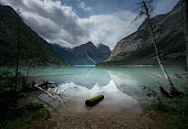 A moody day on the shores of an alpine lake blue with glacial silt in the rocky mountains of Canada