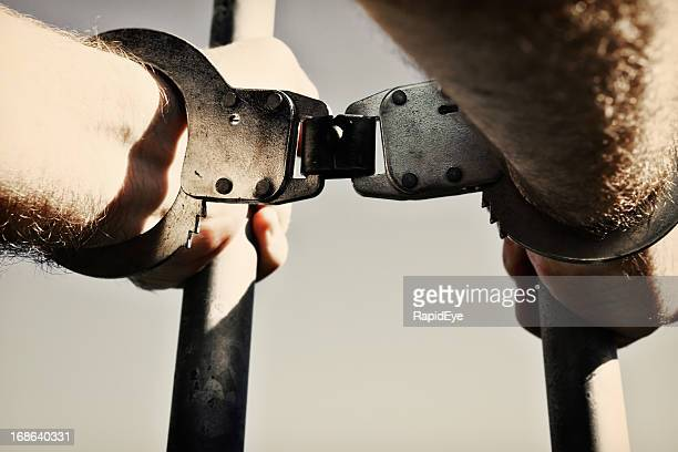 Moody, desaturated image of handcuffed hands clutching prison bars