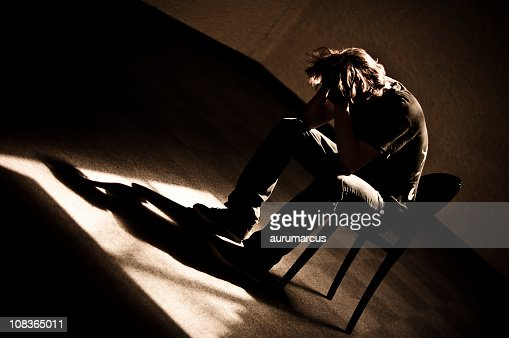 Moody monotone shot of a depressed person slumped in chair