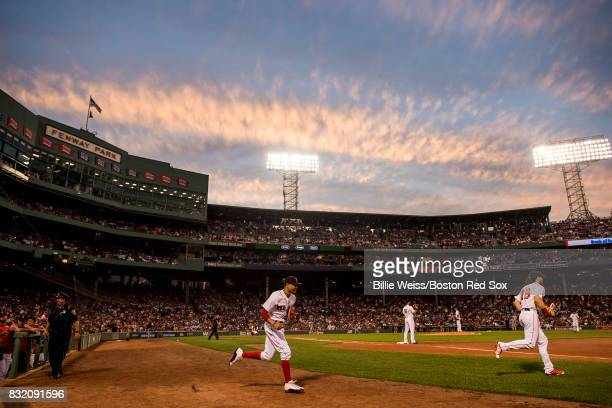 Mookie Betts and Andrew Benintendi of the Boston Red Sox run onto the field as the sun sets during the second inning of a game against the St Louis...