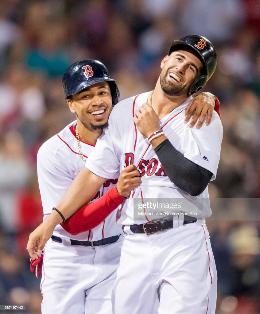 Mookie Betts #50 and Deven Marrero #17 of the Boston Red Sox react after scoring against the Texas Rangers in the sixth inning at Fenway Park on May 23, 2017 in Boston, Massachusetts.