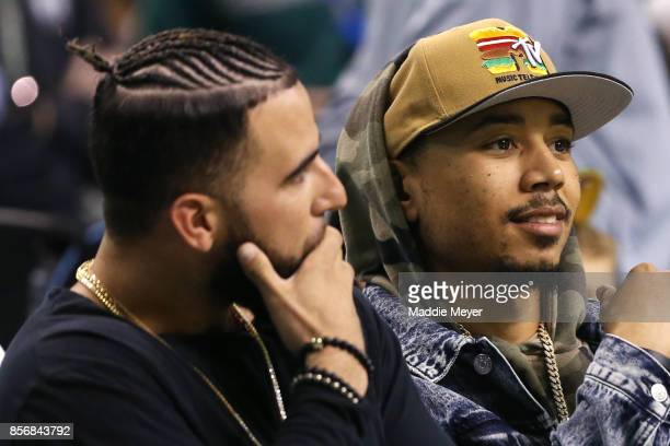 Mookie Betts and Deven Marrero of the Boston Red Sox sit court side during the first half of the game between the Boston Celtics and the Charlotte...