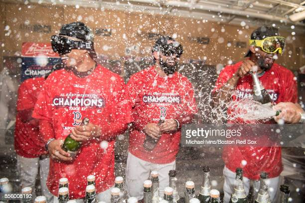 Mookie Betts Deven Marrero and Eduardo Nunez of the Boston Red Sox celebrate after the team clinched the American League East pennant with a win over...