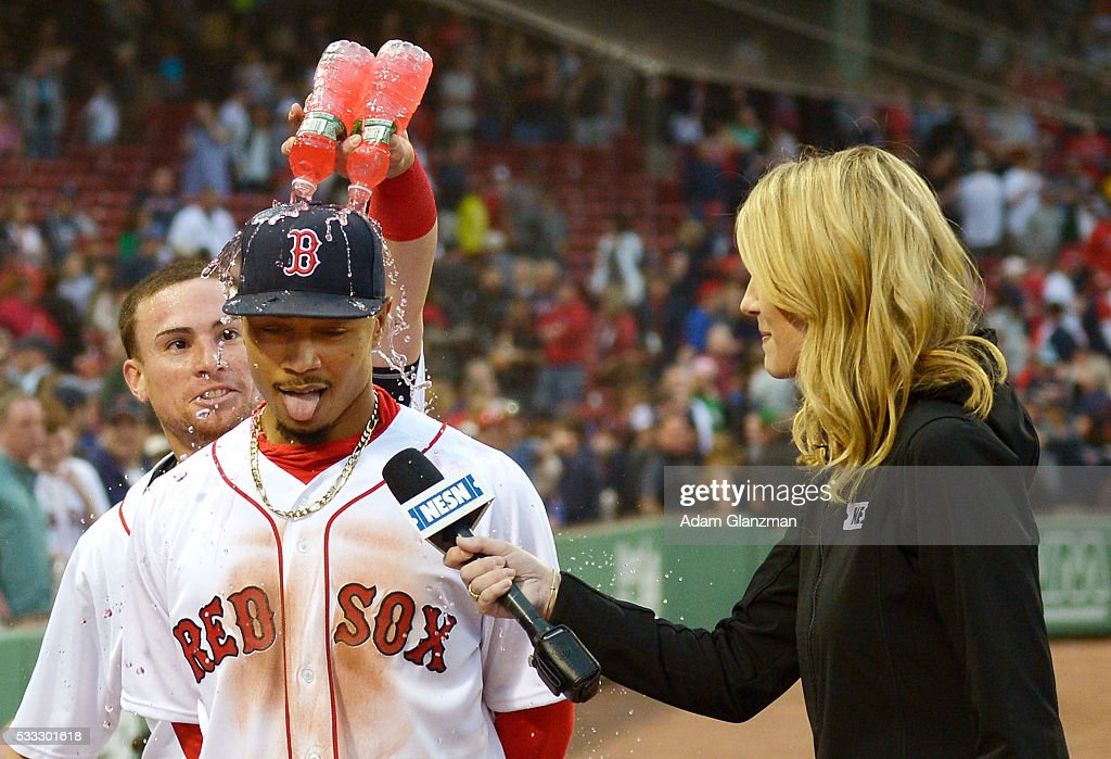 Mookie Betts #50 has water poured on him by Christian Vazquez #7 of the Boston Red Sox after their victory over the Cleveland Indians at Fenway Park on May 21, 2016 in Boston, Massachusetts.