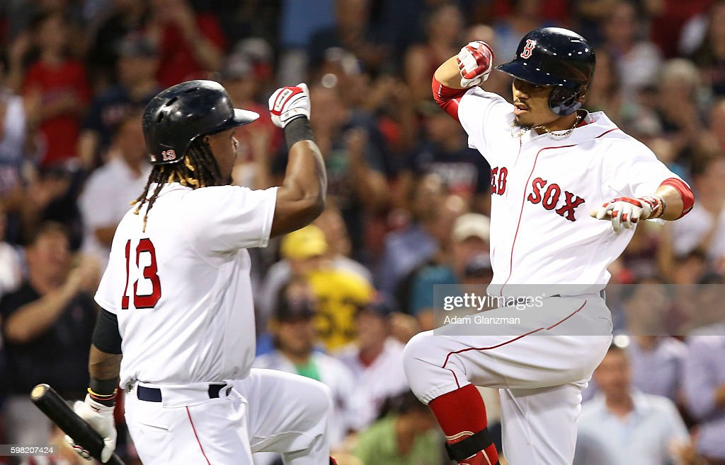 Mookie Betts high fives Hanley Ramirez of the Boston Red Sox after hitting a solo home run in the second inning during a game against the Tampa Bay...