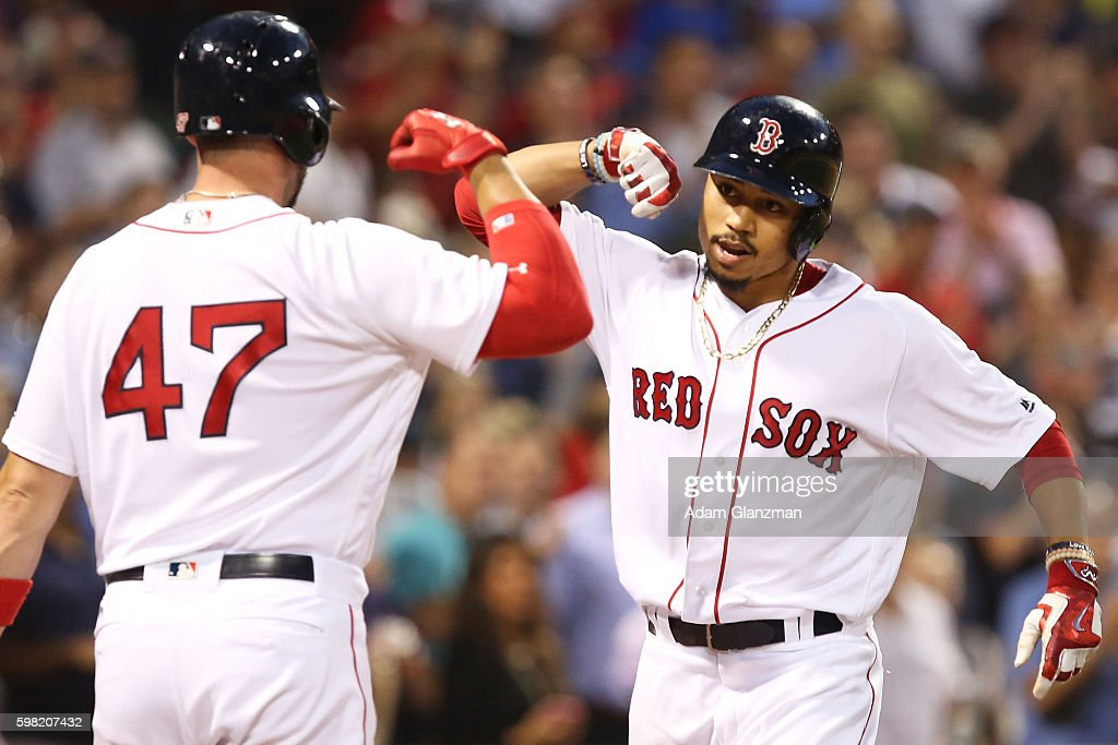 Mookie Betts high fives Travis Shaw of the Boston Red Sox after hitting a solo home run in the second inning during a game against the Tampa Bay Rays...