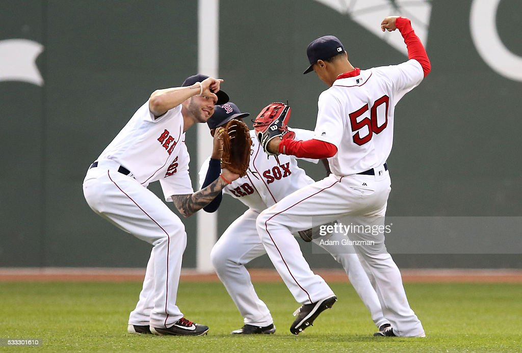 Mookie Betts #50, Jackie Bradley Jr. #25 and Blake Swihart #23 of the Boston Red Sox celebrate after their victory over the Cleveland Indians at Fenway Park on May 21, 2016 in Boston, Massachusetts.