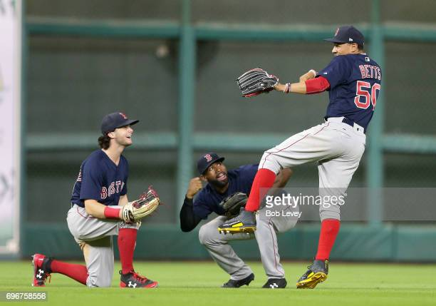 Mookie Betts of the Boston Red Sox along with Jackie Bradley Jr #19 and Andrew Benintendi celebrate after their win over the Houston Astros at Minute...