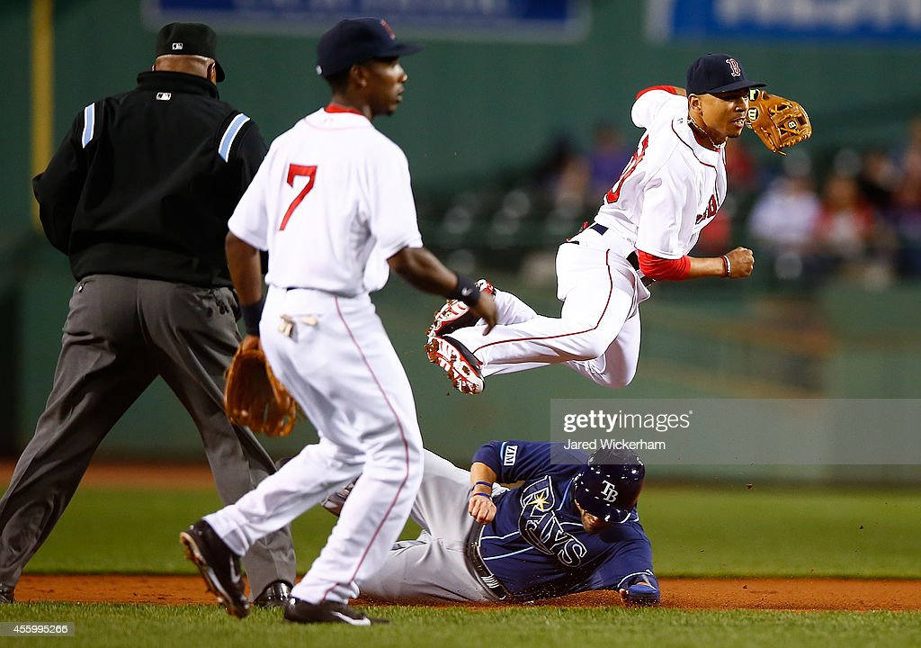 <a gi-track='captionPersonalityLinkClicked' href=/galleries/search?phrase=Mookie+Betts&family=editorial&specificpeople=12732023 ng-click='$event.stopPropagation()'>Mookie Betts</a> #50 of the Boston Red Sox attempts to turn the double play over <a gi-track='captionPersonalityLinkClicked' href=/galleries/search?phrase=David+DeJesus&family=editorial&specificpeople=206765 ng-click='$event.stopPropagation()'>David DeJesus</a> #7 of the Tampa Bay Rays in the first inning during the game at Fenway Park on September 23, 2014 in Boston, Massachusetts.
