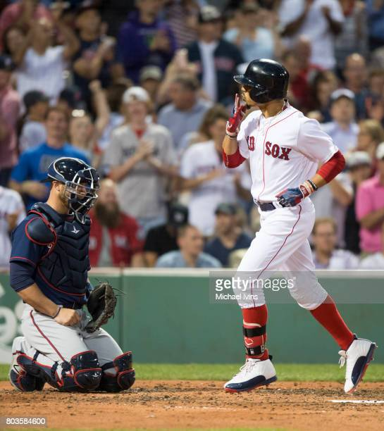 Mookie Betts of the Boston Red Sox blows a kiss while crossing home plate after a home run against the Minnesota Twins in the fourth inning at Fenway...