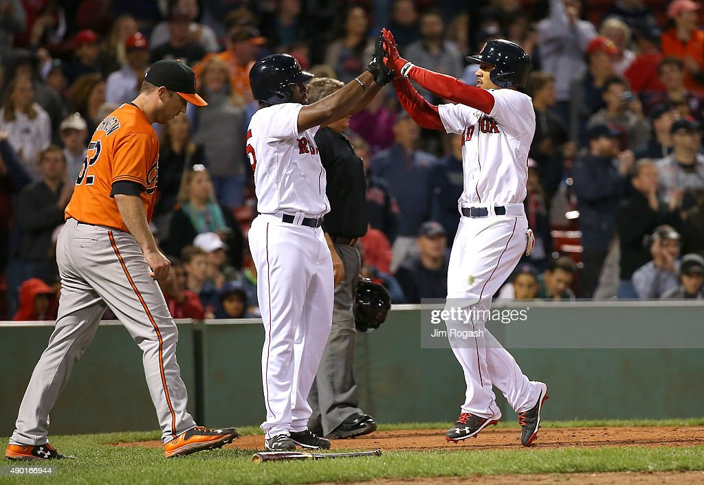 Mookie Betts #50 of the Boston Red Sox celebrates after scoring with Jackie Bradley Jr. #25 as Steve Johnson #52 of the Baltimore Orioles heads back to the mound in thee eighth inning at Fenway Park on September 26, 2015 in Boston, Massachusetts.