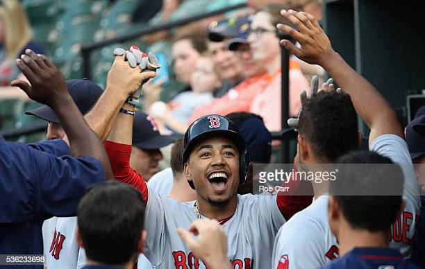 Mookie Betts of the Boston Red Sox celebrates in the dugout after hitting a solo home run against the Baltimore Orioles in the first inning at Oriole...