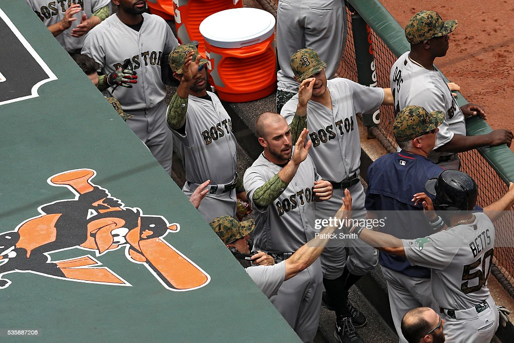 Mookie Betts #50 of the Boston Red Sox celebrates in the dugout with teammates after scoring during the first inning against the Baltimore Orioles at Oriole Park at Camden Yards on May 30, 2016 in Baltimore, Maryland.