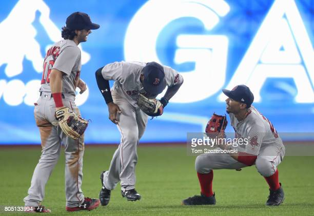Mookie Betts of the Boston Red Sox celebrates their victory with Jackie Bradley Jr #19 and Andrew Benintendi during MLB game action against the...