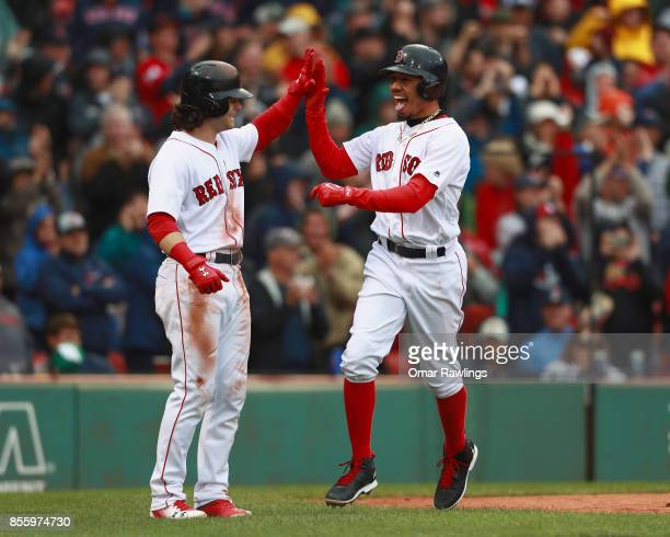 Mookie Betts of the Boston Red Sox celebrates with Andrew Benintendi of the Boston Red Sox after crossing home plate in the bottom of the fifth...