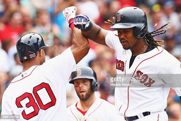 Mookie Betts of the Boston Red Sox celebrates with Chris Young after hitting a grand slam during the fifth inning against the Tampa Bay Rays at...