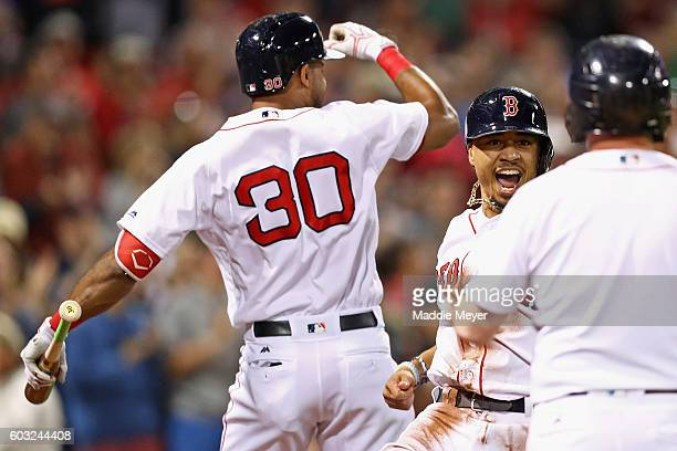 Mookie Betts of the Boston Red Sox celebrates with Chris Young after scoring a run against the Baltimore Orioles during the first inning at Fenway...