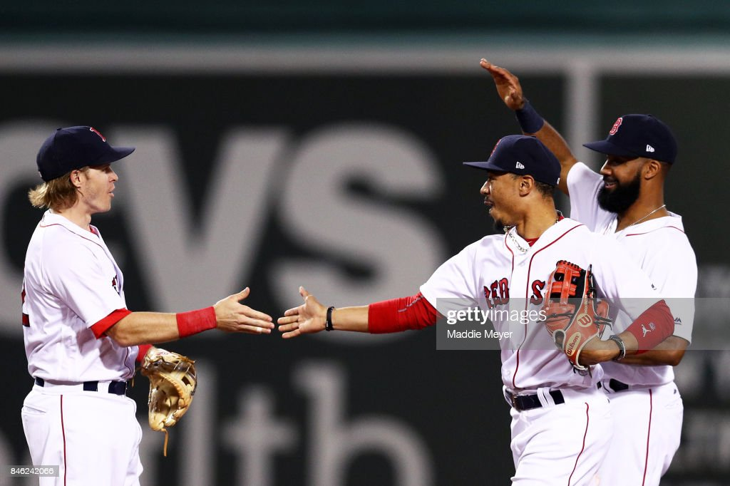 Mookie Betts #50 of the Boston Red Sox celebrates with Chris Young #30 and Brock Holt #12 after defeating the Oakland Athletics 11-1 at Fenway Park on September 12, 2017 in Boston, Massachusetts.