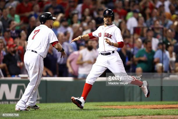 Mookie Betts of the Boston Red Sox celebrates with Christian Vazquez after scoring a run against the Cleveland Indians during the sixth inning at...