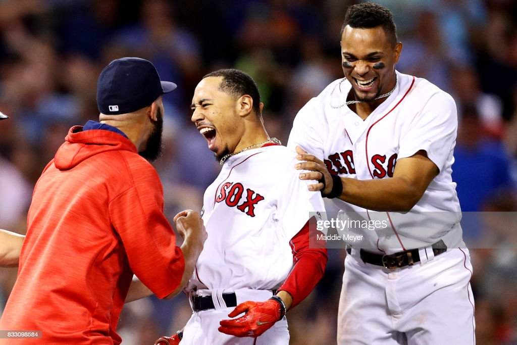 Mookie Betts #50 of the Boston Red Sox celebrates with David Price #24 and Xander Bogaerts #2 after hitting a go ahead two run double to defeat the St. Louis Cardinals 5-4 at Fenway Park on August 16, 2017 in Boston, Massachusetts.