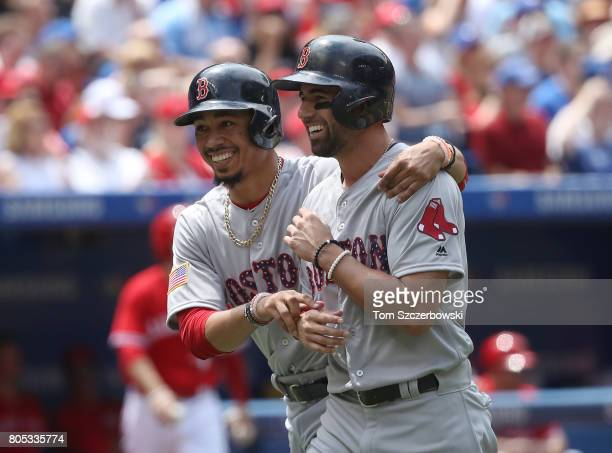 Mookie Betts of the Boston Red Sox celebrates with Deven Marrero after both runners score on a tworun double by Dustin Pedroia in the second inning...